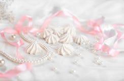 Francuscy bez ciastka dla ślubnego tła z perłami, menchiami i biel atłasowymi faborkami, koronką i Obrazy Royalty Free