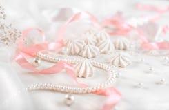 Francuscy bez ciastka dla ślubnego tła z perłami, menchiami i biel atłasowymi faborkami, koronką i Fotografia Royalty Free