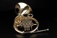 Francuski róg na drewnianym stole Piękny okrzesany instrument muzyczny zdjęcia royalty free