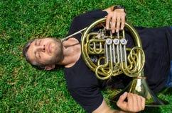 francuski róg Mężczyzna w koszulce kłama na trawie i trzyma instrument muzycznego Waldhorn zdjęcia stock