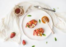 Francuskie grzanki z truskawką, kremowym serem, miodem i mennicą na lekkim ceramicznym talerzu, Obraz Stock