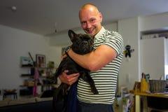 Francuskiego buldoga szczeniak i uśmiechnięty mężczyzna Fotografia Stock