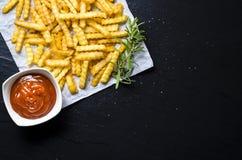 Francuzów dłoniaki z ketchupem nad zmroku stołem zdjęcia stock