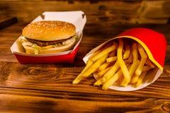 Francuza hamburger na drewnianym stole i dłoniaki obrazy stock
