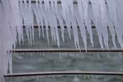 Frangia del ghiacciolo sulle inferriate del metallo vicino al mare Immagini Stock