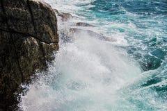 Frangiflutti contro la roccia Immagine Stock