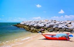 Frangiflutti e barca a remi di pietra alla spiaggia Fotografia Stock