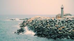 Frangiflutti e faro concreti nel paesaggio del mare Segnale in mare tempestoso video d archivio