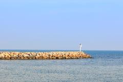Frangiflutti nel mare con faro rotante su  Fotografia Stock Libera da Diritti