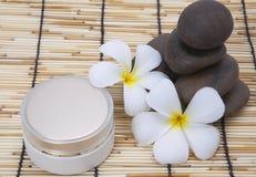 Frangipani spa set, moisturizer, polished stone. Stock Image