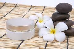 Frangipani spa set, moisturizer, polished stone. Stock Photography