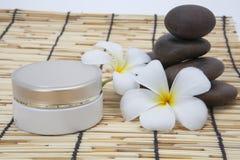 Frangipani spa set, moisturizer, polished stone. Royalty Free Stock Image