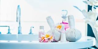 Frangipanien blommar med växt- kompressstämplar, rosa lotionflaska på lyxigt bad Spa eller wellness Arkivfoto