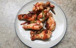 frango frito com alho e pimentões no prato no backgro concreto Imagens de Stock