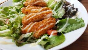 Frango frito panado com o tomate verde orgânico da salada de caesar na tabela de madeira no restaurante ocidental Foto de Stock