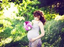 Frank bekymmerslös förtjusande gravid kvinna i fält med blommor på Arkivbilder