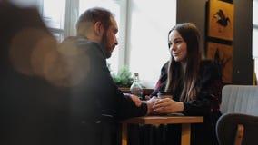 Frank bild av unga par i en coffee shop Caucasian man och kvinna som sitter med en hund i ett kafé Långt skott av vinden arkivfilmer