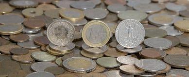 Frank, euro et dollar sur le fond de beaucoup de vieilles pièces de monnaie Photo stock