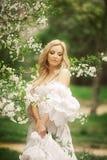 Frank hoppande over carefree förtjusande kvinna i fält med blommor på sommarsolnedgången fotografering för bildbyråer