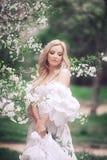 Frank hoppande over carefree förtjusande kvinna i fält med blommor på sommarsolnedgången royaltyfri bild