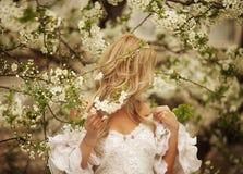 Frank hoppande over carefree förtjusande kvinna i fält med blommor på sommarsolnedgången arkivfoto