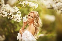 Frank hoppande over carefree förtjusande kvinna i fält med blommor på sommarsolnedgången arkivfoton