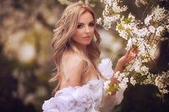 Frank hoppande over carefree förtjusande kvinna i fält med blommor på sommarsolnedgången royaltyfri foto