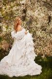 Frank hoppande over carefree förtjusande kvinna i fält med blommor på sommarsolnedgången royaltyfri fotografi