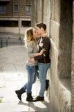 Frank stående av härliga europeiska par med förälskat kyssa för ros på gatagränden som firar valentindag royaltyfri foto