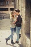 Frank stående av härliga europeiska par med förälskat kyssa för ros på gatagränden som firar valentindag Arkivbilder