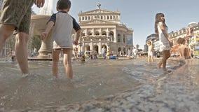 Frankfurt, Duitsland - Augustus 02 2018: Mensen die naar verfrissing in het water van de fontein in Opernplatz zoeken tijdens stock video