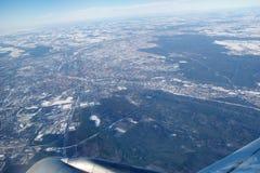FRANKFURT, DUITSLAND - 20 JANUARI, 2017: De mening door vliegtuigenvenster op straalvleugel, wingview over sneeuw bedekte stad va Stock Foto's