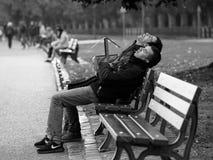 Frankfurt Gemany - Oktober 24: Oidentifierade män sover på bänk på sjön på Oktober 24, 2015 i Frankfurt, Tyskland Royaltyfria Bilder