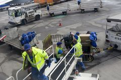Loaders at the airport unload baggage from the aircraft. FRANKFURT, GERMANY - September 12, 2017 Loaders at the airport unload baggage from the aircraft Royalty Free Stock Photo