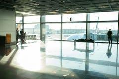 Frankfurt-am-Main, Duitsland - Oktober 11, 2015: de mensen wachten op op vlucht in luchthaven bij groot vensterglas Toeristenpass stock foto's
