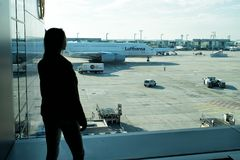Frankfurt-am-Main, Duitsland - Oktober 11, 2015: het meisjessilhouet bekijkt vliegtuigen op vliegveldgrond op zonnige dag Vrouw i royalty-vrije stock fotografie