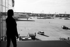 Frankfurt-am-Main, Duitsland - Oktober 11, 2015: Vrouw in luchthaven Het meisjessilhouet bekijkt vliegtuigen op vliegveldgrond stock fotografie