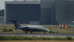 Private airplane prepares to take off. FRANKFURT AM MAIN, GERMANY - JULY 21, 2017: Private airplane Piaggio P180 Avanti warms up engines on runway and going to stock footage