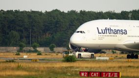 Towing Lufthansa Airbus 380. FRANKFURT AM MAIN, GERMANY - JULY 18, 2017: The tractor tows Lufthansa Airbus 380 D-AIMN named -Deutchland- from service. Fraport stock footage
