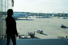 Frankfurt am Main, Germany - October 11, 2015: woman in airport. Girl silhouette look at planes on airdrome ground on sunny day. T. Raveling by air. Aviation Royalty Free Stock Photos