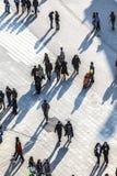 Ludzie chodzi przy ulicą z długimi cieniami Obrazy Royalty Free