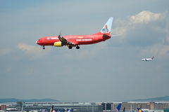 FRANKFURT TYSKLAND - JULI 09., 2017: TUIfly FLYGBOLAG Boeing 737-800 med den röda annonseringen landar med en annan nivå in Arkivbilder