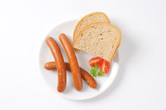 Frankfurter sausages and bread. Hot frankfurter sausages and slice of bread on white plate Royalty Free Stock Photos