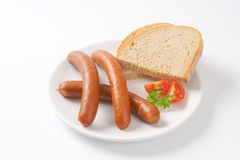 Frankfurter sausages and bread. Hot frankfurter sausages and slice of bread on white plate Royalty Free Stock Photography