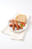 Frankfurter sausages and bread. Hot frankfurter sausages and slice of bread on white plate Royalty Free Stock Photo