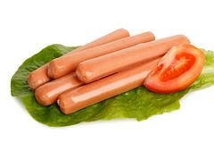 Frankfurter sausages. Raw frankfurter sausages on lettuce leaf with tomato slice isolated on white Stock Images