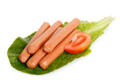Frankfurter sausages. Raw frankfurter sausages on lettuce leaf with tomato slice isolated on white Royalty Free Stock Photo