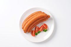 Frankfurter sausages. Raw frankfurter sausages on white plate Royalty Free Stock Photography