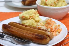 Frankfurters. Large frankfurters with carrot and cabbage coleslaw and mash for dinner Royalty Free Stock Photography