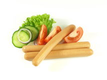 Frankfurters on isolated background. Close-up of frankfurters with decoration, tomato and cucumber Stock Photo